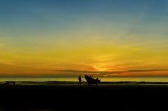 Pescador en la playa durante salida del sol Imagenes de archivo