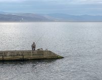 Pescador en la playa en el otoño en la Crimea Fotos de archivo