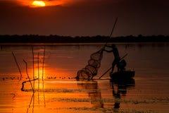 Pescador en la puesta del sol Foto de archivo libre de regalías