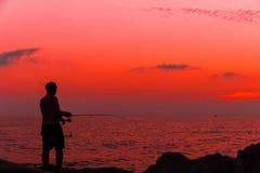 Pescador en la puesta del sol cerca del mar Foto de archivo