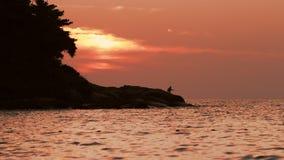 Pescador en la puesta del sol roja almacen de metraje de vídeo