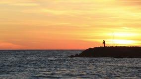 Pescador en la puesta del sol en un rompeolas almacen de metraje de vídeo