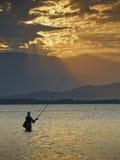 Pescador en la salida del sol Imagenes de archivo