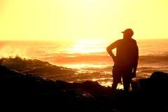 Pescador en las rocas en la salida del sol Foto de archivo