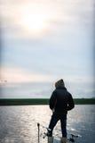 Pescador en luz del sol cerca de dos cañas de pescar que esperan los pescados Imágenes de archivo libres de regalías