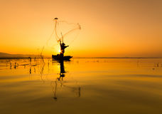Pescador en pescados de madera de la captura de la silueta del barco en el lago por la mañana Fotos de archivo libres de regalías