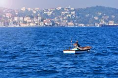Pescador en un bote pequeño en el mar fotografía de archivo