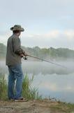 Pescador en un lago brumoso de la mañana Fotos de archivo