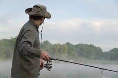 Pescador en un lago brumoso de la mañana Fotografía de archivo libre de regalías