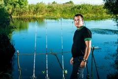 Pescador en un lago con las cañas de pescar Fotografía de archivo libre de regalías