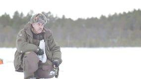 Pescador en una pesca congelada del hielo del lago almacen de video