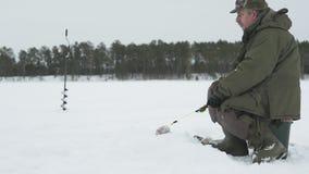 Pescador en una pesca congelada del hielo del lago almacen de metraje de vídeo