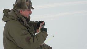 Pescador en una pesca congelada del hielo del lago metrajes