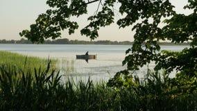 Pescador en una pesca del barco en un lago metrajes