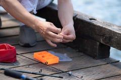 Pescador fêmea que prepara a vara de pesca fotografia de stock