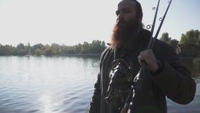 Pescador farpado com caminhadas longas da barba no banco de rio com varas de pesca Movimento lento vídeos de arquivo