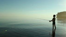 Pescador joven en la pesca de lago metrajes