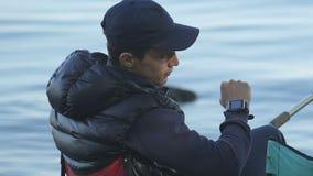 Pescador joven que mira su reloj elegante, comprobando tiempo y temperatura metrajes