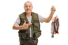 Pescador maduro alegre que guarda peixes recentemente travados e apontar Foto de Stock Royalty Free