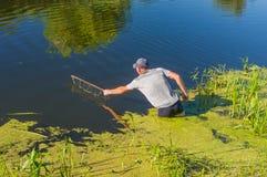 Pescador maduro que examina la pequeña red en el río Merla en el día de verano Imagen de archivo libre de regalías
