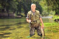 Pescador maduro que sostiene pescados en un río Fotos de archivo libres de regalías