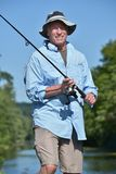 Pescador masculino adulto feliz With Rod And Reel Outdoors imagens de stock royalty free