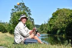 Pescador masculino aposentado de sorriso With Rod And Reel Outdoors imagem de stock royalty free