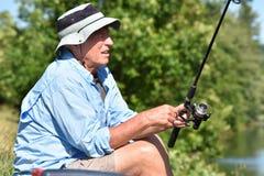 Pescador masculino aposentado sério With Fishing Rod Outdoors foto de stock