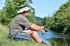 Pescador masculino aposentado Sitting With Fishing Rod Outdoors fotos de stock royalty free