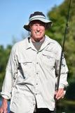 Pescador masculino aposentado Smiling With Rod And Reel Outdoors fotos de stock royalty free