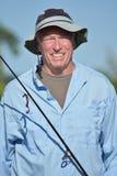 Pescador masculino de sorriso With Fishing Rod Outdoors do aposentado foto de stock