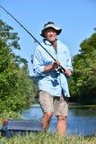 Pescador masculino estando With Rod And Reel Outdoors do aposentado idoso fotografia de stock
