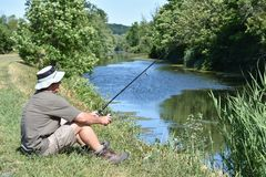 Pescador masculino Resting With Fishing Rod Outdoors imagens de stock