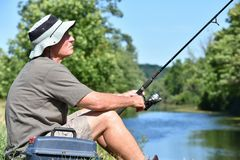 Pescador masculino superior Sitting With Rod And Reel Outdoors imagem de stock