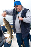 Pescador mayor con el trofeo imagenes de archivo