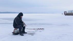 Pescador mayor en la ropa oscura que pesca en la caña de pescar del invierno en el río congelado almacen de metraje de vídeo