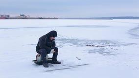 Pescador mayor en la ropa oscura que pesca en la caña de pescar del invierno en el río congelado en el fondo del puerto fluvial almacen de video