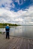 Pescador mayor en un embarcadero Foto de archivo libre de regalías