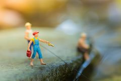 Pescador miniatura que se sienta en la piedra, pescando en el río Foto macra de la visión, uso como concepto de la carrera de la  Fotos de archivo