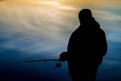 Pescador na pesca do por do sol fotografia de stock