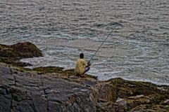 Pescador nas pedras Fotos de Stock