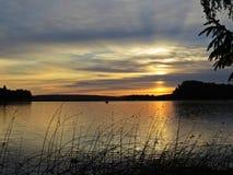 Pescador no barco atrás dos juncos no por do sol sobre o lago bonito com o céu nebuloso no fundo fotos de stock royalty free