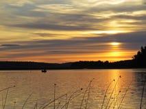 Pescador no barco atrás dos juncos no por do sol sobre o lago bonito com o céu nebuloso no fundo imagem de stock