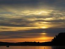 Pescador no barco atrás dos juncos no por do sol sobre o lago bonito com o céu nebuloso no fundo fotografia de stock royalty free