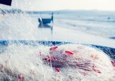 Pescador no barco com rede nas mãos imagem de stock