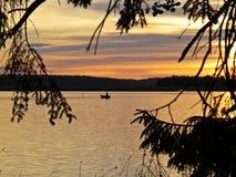 Pescador no barco entre ramos de árvore no por do sol sobre o lago bonito com o céu nebuloso no fundo fotos de stock royalty free