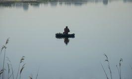 Pescador no barco Homem com giro Fotos de Stock