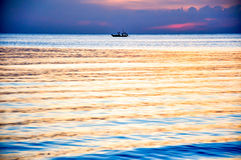 Pescador no barco no céu crepuscular Fotos de Stock