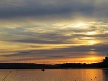 Pescador no barco no por do sol sobre o lago bonito com o céu nebuloso no fundo imagem de stock