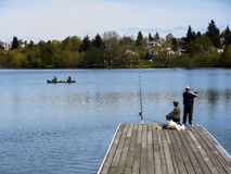 Pescador no cais; dois em uma canoa Tudo em um lago Fotos de Stock Royalty Free